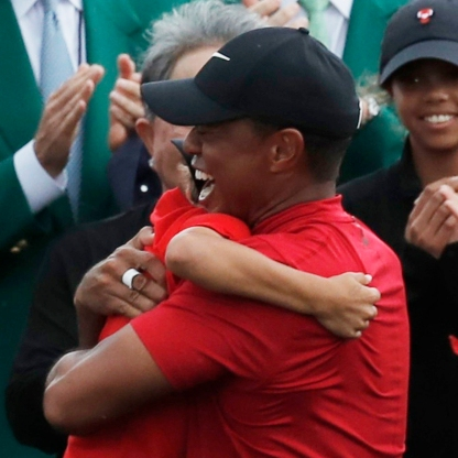 Golf - Masters - Augusta National Golf Club - Augusta, Georgia, U.S. - April 14, 2019 - Tiger Woods of the U.S. embraces his son Charlie Axe as his daughter Sam Alexis (R) looks on after he won the 2019 Masters.